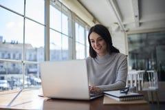 Indépendant féminin attirant de sourire réalisant le travail à distance utilisant l'ordinateur portable Image stock
