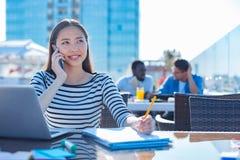 Indépendant féminin parlant avec l'ami au téléphone Photo libre de droits