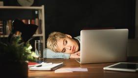 Indépendant fatigué travaillant sur l'ordinateur portable à la maison jusqu'à fin de soirée Images stock