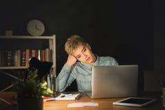 Indépendant fatigué travaillant sur l'ordinateur portable à la maison jusqu'à fin de soirée Photographie stock