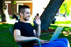 Indépendant heureux d'homme ayant la conférence de webcam par l'intermédiaire du dispositif de carnet photographie stock libre de droits