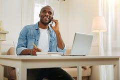 Indépendant heureux parlant sur le téléphone et le travail Image libre de droits