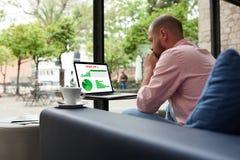 Indépendant inquiété à la pause-café utilisant le carnet pour l'évaluation de performances des périodes récentes Photo stock