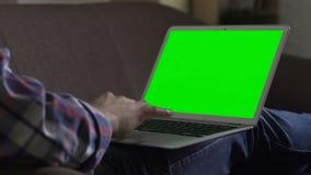 Indépendant masculin s'asseyant sur le divan avec l'ordinateur portable, Internet surfant dans le temps gratuit banque de vidéos