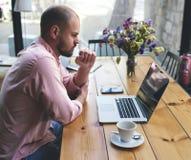 Indépendant masculin se reliant à la radio par l'intermédiaire de l'ordinateur portable Image libre de droits
