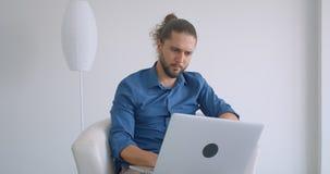 Indépendant progressif travaillant avec l'ordinateur portable se reposant dans le fauteuil dans le bureau confortable et léger banque de vidéos