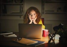 Indépendant travaillant sur l'ordinateur portable à la maison jusqu'à fin de soirée Image libre de droits