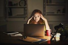 Indépendant travaillant sur l'ordinateur portable à la maison jusqu'à fin de soirée Photo libre de droits