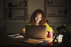 Indépendant travaillant sur l'ordinateur portable à la maison jusqu'à fin de soirée Images libres de droits