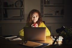 Indépendant travaillant sur l'ordinateur portable à la maison jusqu'à fin de soirée Photo stock