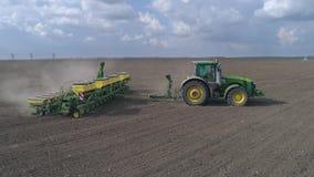 Indústria agrícola, trator durante a aradura de passeios através do grande campo marrom com os arados no fundo do céu azul filme