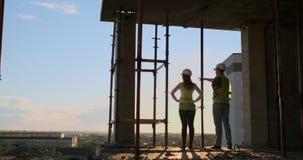 Indústria da construção: conceito dos trabalhos de equipe: Posição nova do coordenador atrás de olhar um terreno de construção, v filme