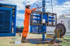A indústria de petróleo e gás a pouca distância do mar, trabalhador da plataforma petrolífera inspeciona e settin imagens de stock