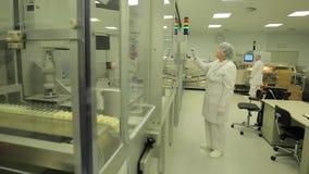 Indústria farmacêutica Operário masculino que inspeciona a qualidade dos comprimidos que empacotam na fábrica farmacêutica automá filme