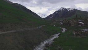 Indagine di aria sopra il villaggio di Ushguli Sopra i tetti delle case, dei posti di guardia e di un fiume della montagna, Georg stock footage