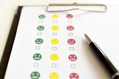 Indagine di valutazione di servizio di assistenza al cliente con i fronti sorridente e la penna immagini stock