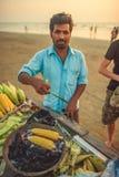 Inde, Goa - 26 novembre 2016 : L'homme fait cuire le maïs sur le charbon de bois photos stock
