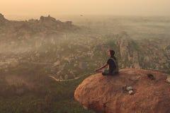 Inde, Hampi - 22 décembre 2015 : Un homme pratique le yoga sur le dessus de la falaise pendant l'aube Photographie stock
