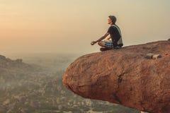 Inde, Hampi - 22 décembre 2015 : Un homme pratique le yoga sur le dessus de la falaise pendant l'aube Image libre de droits