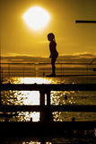 Indecision little girl silhouette on the 3m springboard. Royalty Free Stock Photography