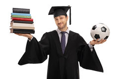 Indecisive graduate student holding books and a football Stock Photography