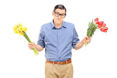 Indecisive man holding red and yellow tulips Royalty Free Stock Photos