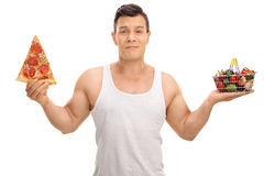 Indecisive man holding small shopping basket and pizza slice. Indecisive young man holding a small shopping basket full of fruits and vegetables and a pizza Royalty Free Stock Images