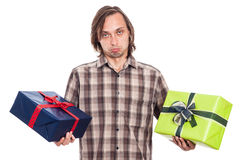 Indecisive man with two gifts. Indecisive man holding two gift boxes, isolated on white background Stock Photos