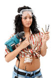 Indecisive repair woman. A sexy female worker with a drilling machine in one hand and three drill-bits in the other hand Royalty Free Stock Photo