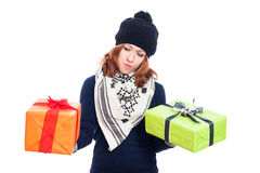 Indecisive woman with presents. Indecisive winter woman holding two presents, isolated on white background Royalty Free Stock Images