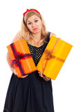 Indecisive woman with two gifts. Indecisive woman holding two gift boxes, isolated on white background Royalty Free Stock Image