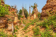 Indein, Inle Lake. Path between ancient Stupas at Indein overgrown with plants, Inle Lake, Myanmar Stock Image