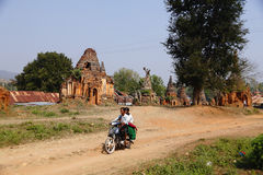Indein in Myanmar. The man driver a motorbike passing the Shwe Indein, Inle Lake, Myanmar Stock Photos