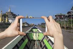 Indein Village photo with smartphone. Tourist taking a photo with smartphone on a boat while visiting Indein Village in Myanmar Royalty Free Stock Image