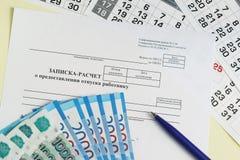 Indemnité de congés payés Note-calcul sur l'octroi des vacances au travailleur, au stylo et à l'argent russe Photos libres de droits