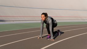 Independed-Brunettefrau, die für den Lauf auf der Läuferbahn sich vorbereitet stockfotos