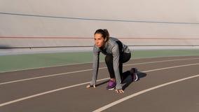 Independed brunettkvinna som förbereder sig för körningen på löparespåret arkivfoton