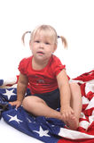 Independence Day. Adorable little girl sitting on American flag Royalty Free Stock Images