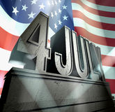Independence day. July 4 in silver letters on a silver pedestal   in sunbeams in front of the american flag Royalty Free Stock Photos