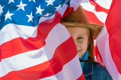 Independence Day. Beautiful happy girl with green eyes on the background of the American flag on a bright sunny day royalty free stock photo