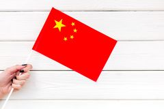 Independence Day of China concept with flag in hand on white wooden background top view.  stock photo