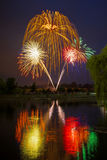 Independence Day Fireworks Reflected in Water with a willow tree Stock Photo