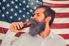 Independence day man with flag and coca cola. Ukraine, Kyiv - July 27, 2016: young patriotic happy bearded man with long blue beard on american flag background royalty free stock images