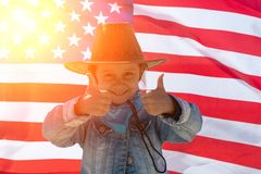 Independence Day. Patriotic holiday. Happy kid, cute little child girl with American flag. Cowboy stock photography
