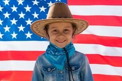 Independence Day. Patriotic holiday. Happy kid, cute little child girl with American flag. Cowboy stock image