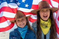 Independence Day. Patriotic holiday. Happy kids, cute two girls with American flag. Cowboy. USA celebrate 4th of July royalty free stock photos