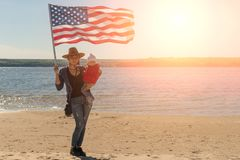 Independence Day. Patriotic holiday. A woman in a cowboy hat with a baby in her arms and with an American flag stock image