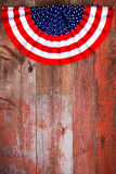 Independence Day patriotic rosette. To commemorate the signing of the Declaration of Independence on the 4th July lying on rustic wooden boards with plenty of Stock Image