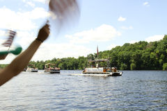 Independence day pontoon parade passes by on river Stock Image