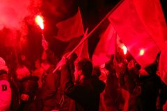 Independence Day March in Warsaw Poland Marred by Violence and Controversy. Independence Day Protester holds high a flare underneath the Polish flag Royalty Free Stock Photos